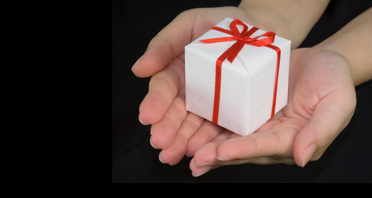 small white box wrapped with red ribbon in palm of hands